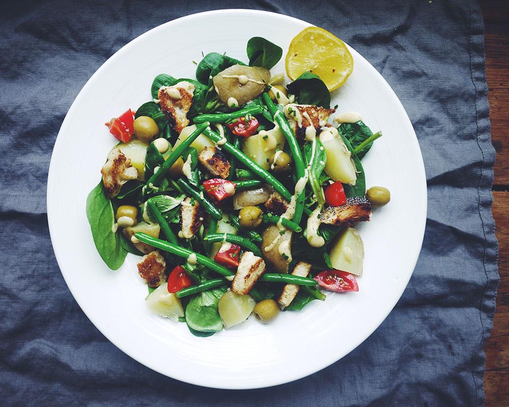 Sallad på potatis, haricots verts, brödkrutonger, dijondressing och gröna blad